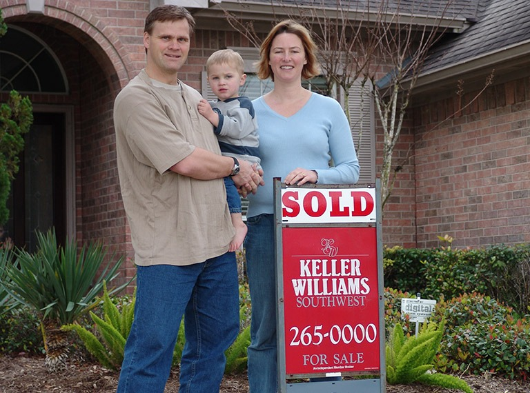 Photo of a family infront of a Fort Bend area home with a sold real estate sign